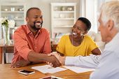 Mature black husband shaking hands with senior agent on taking loan. Happy african couple sealing wi poster