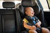 Portrait of cute smiling toddler sitting in car seat and looking outside the window. Little boy sitt poster