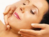 Young woman lying on her back, gets massage,reiki,on her face
