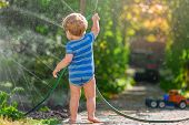 A Little Boy In A Blue Bodysuit, Barefoot, Soiling His Feet, Plays With A Water Hose Outside, In Sum poster