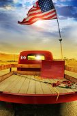 stock photo of truck farm  - Concept photo of a vintage red vintage pick up truck with American flag waving above against rural dramatic cloudscape - JPG