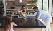 Front view of happy Caucasian family preparing vegetable salad in kitchen at home poster