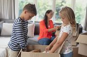Side view of Caucasian siblings unpacking cardboard box while Caucasian mother looking a document in poster