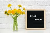 Hello Monday Words On Black Letter Board And Bouquet Of Yellow Dandelions Flowers On Table Against W poster