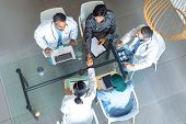 High angle view of diverse medical team working together at table in hospital. Coffee cup, medical f poster