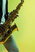 Young African-american Jazz Musician Playing The Saxophone On Gradient Yellow-green Studio Backgroun poster