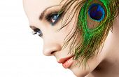 foto of female peacock  - Woman with colorful makeup and peacock feather - JPG