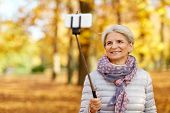 old age, retirement and technology concept - happy senior woman taking picture by selfie stick at au poster