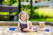 Cute Toddler Girl Playing In Sand On Outdoor Playground. Beautiful Baby In Red Trousers Having Fun O poster