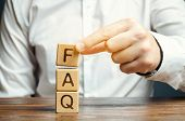 Businessman Puts Wooden Blocks With The Word Faq (frequently Asked Questions). Collection Of Frequen poster