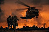 2 Soldiers Helping Wounded Soldier Between Dust In Battle Field To Board The Helicopter poster