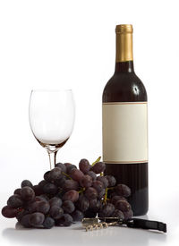 picture of wine-glass  - Grapes wine a wine glass and a wine opener on a white background with copy space - JPG