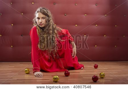 girl sitting near christmass balls
