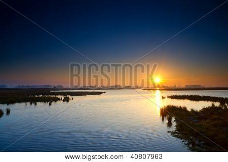 Sun Rising Up Over Blue Lake