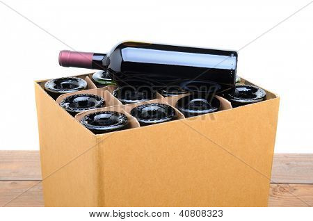 Closeup of a case of wine with one bottle resting on top. Case is sitting on a wood table top with a white background.