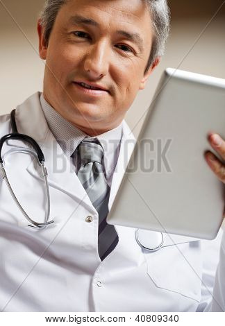 Portrait of mature male doctor in lab coat with digital tablet