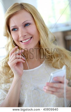 Smiling blond woman talking on cellphone with handsfree