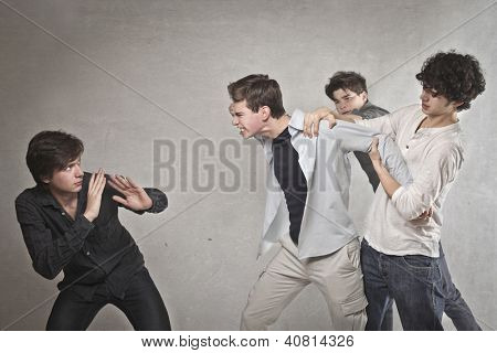 Two guys are quarreling, one of these is held by two friends