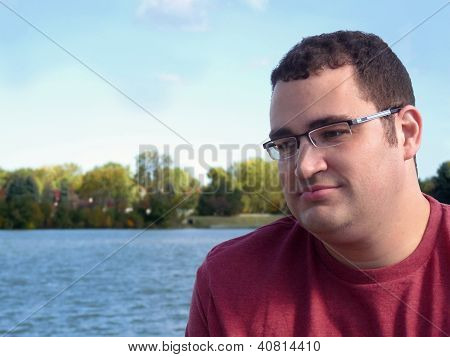 Young Hispanic man by lake.