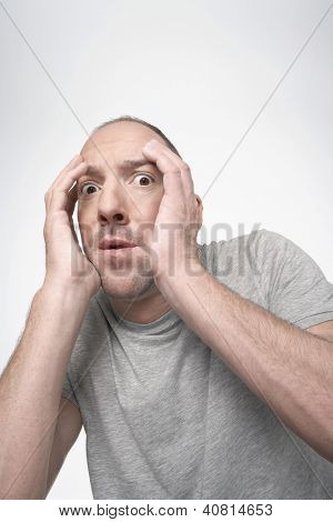 Scared man with hands covering face isolated over white background