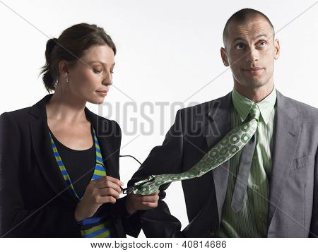 Businesswoman cleaning glasses on tie of businessman over white background
