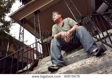 Middle aged man sitting on the steps of a house