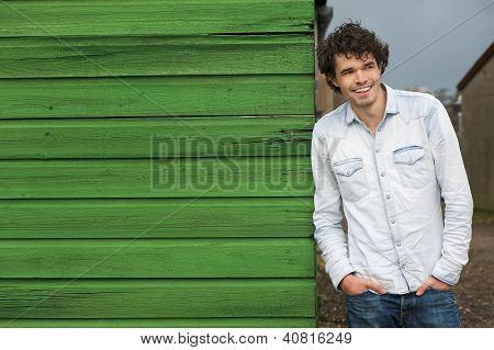 Casual Guy Leaning Against Green Wall