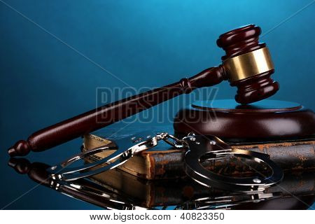 Gavel, handcuffs and book on law on blue background