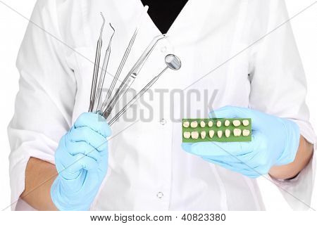 dentists hands in blue medical gloves with dental tools and denture