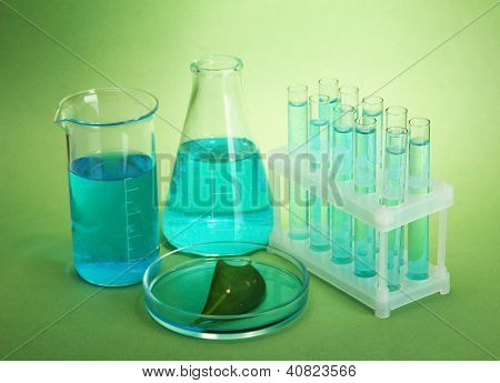 test-tubes and leaf tested in petri dish on green background
