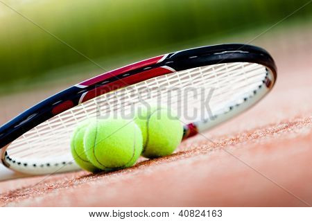 Tennis racket with balls on clay tennis court