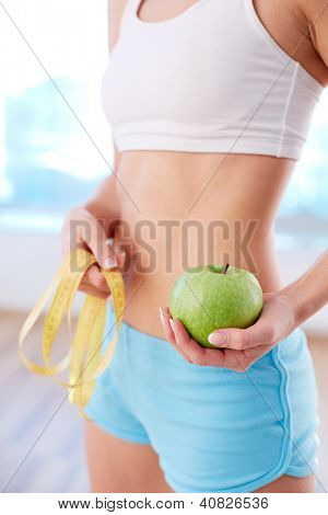 Vertical image of fit female holding green apple in hand