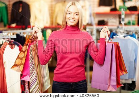 Retrato de um cliente feliz com paperbags olhando para câmera no shopping