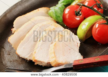 juicy roasted chicken breast with side dish, in the pan