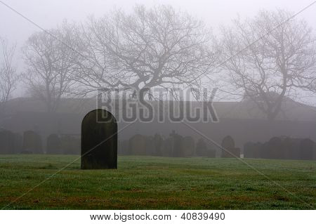 Single Gravestone In A Spooky Graveyard On A Foggy Day