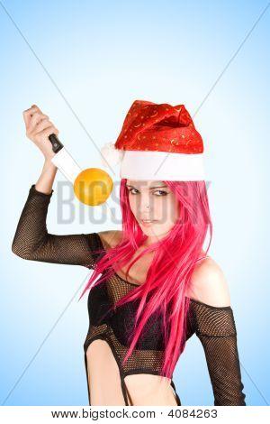 Atractiva señora Santa con naranja en el cuchillo