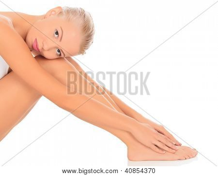 Young woman sitting on floor, white background