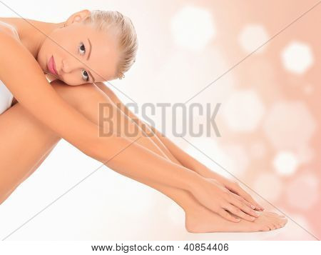 Young woman sitting on floor, pastel blurred background.