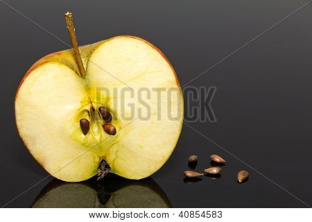 half of apple with some pips on dark background