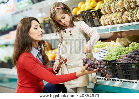 Family food shopping. Young woman mother and little girl daughter choosing fruits grape in supermarket