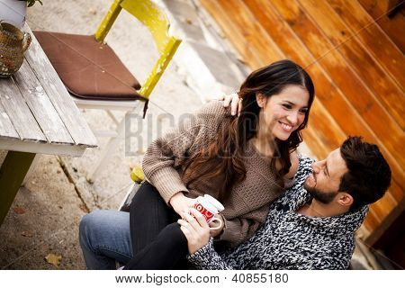Young couple having breakfast in a romantic cabin outdoors in winter.