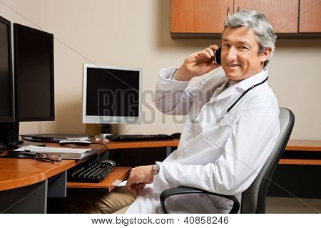 Portrait of happy mature male doctor answering phone call while sitting by desk in clinic