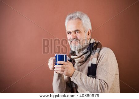 Smiling senior in scarf with a cup