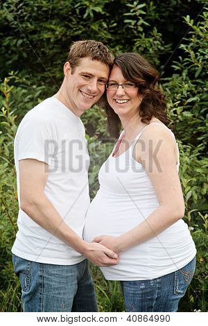 Maternity photos of a couple with brink wall as a background - 8 months pregnant