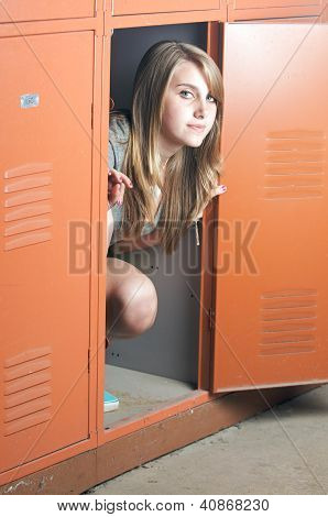 Teenage girl sits in a locker