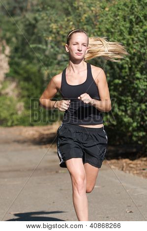 Young woman in black jogs outside
