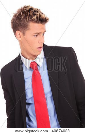 young business man looking to his side and being a little surprised
