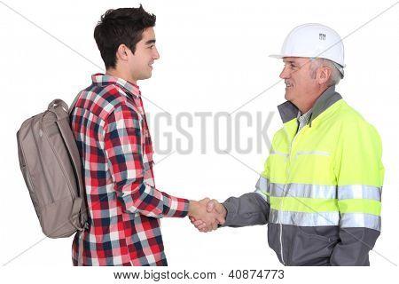 Builder welcoming apprentice