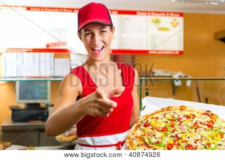 Woman holding a whole pizza in hand and asking you to ordering a pizza