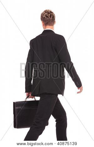 Business man Walking forward and looking to a side while talking on the phone and carrying a briefcase over white background